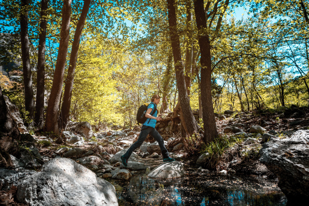 Active woman hiking jumping over a creek in spring, Central Macedonia Greece
