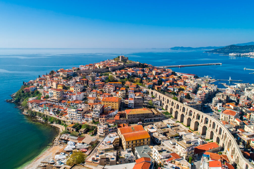 Aerial view the city of Kavala in northern Greek, ancient aqueduct Kamares, homes and medieval city wall, Macedonia Greece