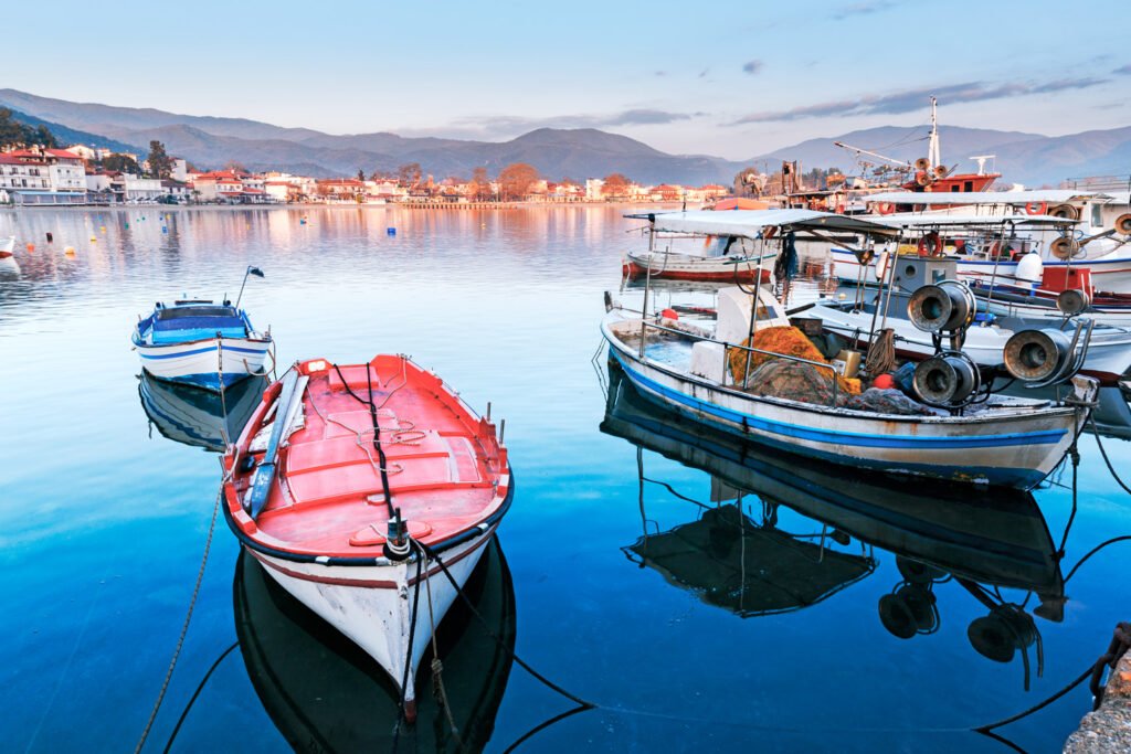 Evening scenery in Kavala sea port, famous and popular resort in northern part of Greece. View over coastline, anchored fishing boats