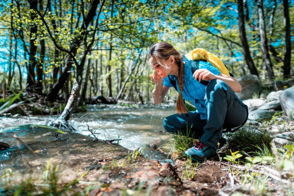 Woman refreshing herself with fresh water from clear creek while hiking, Serres, Central Macedonia Greece