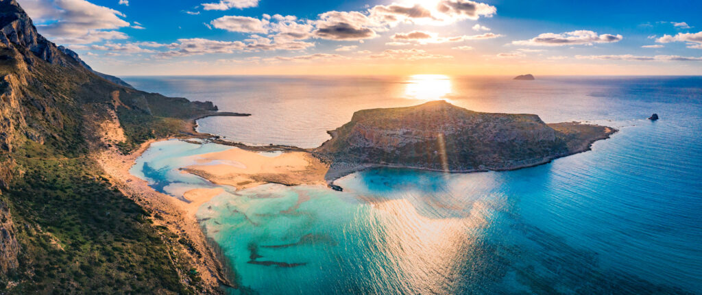 Amazing aerial view of Balos Lagoon with magical turquoise waters, lagoons, tropical beaches of pure white sand and Gramvousa island on Crete, Greece