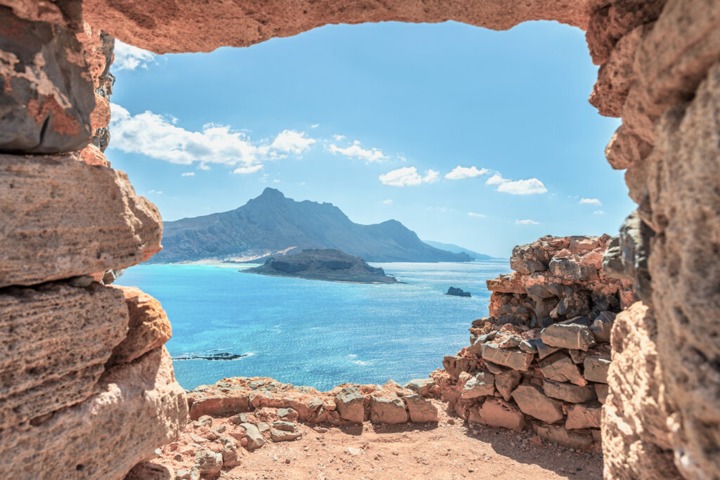 Aerial panoramic view through stone arch of an ancient Venetian castle on the beautiful islet of Imeri Gramvoussa near the beach of Balos in Chania region, Crete Greece