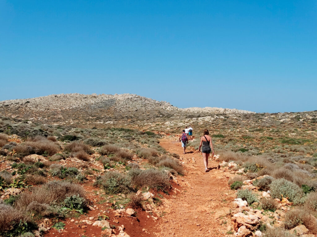 Tourists visit Balos in Crete, hiking toward to the beach. The Gramvousa Peninsula forms the westernmost of the two pairs of peninsula in Crete and the western part of Kissamos Bay.