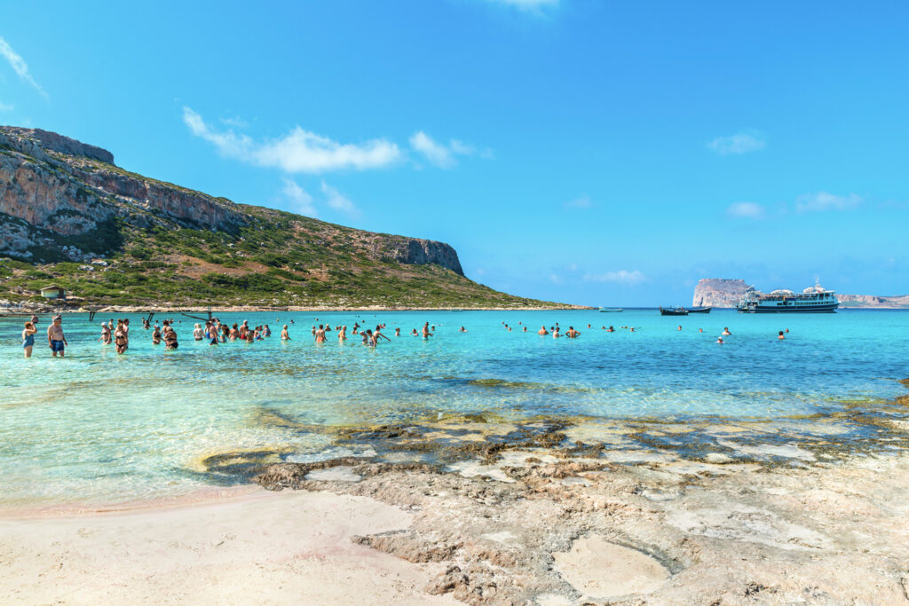 Tourists relax and bathe in crystal clear emerald water of the famous Bay of Balos.The pirate island of Imeri Gramvousa on backdrop, Chania region, Crete