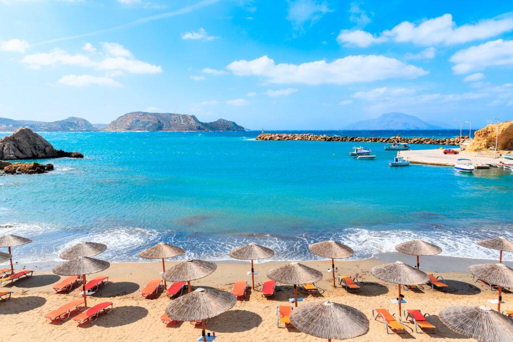 Umbrellas and sunbeds on Finiki beach in Karpathos, Dodecanese Greece
