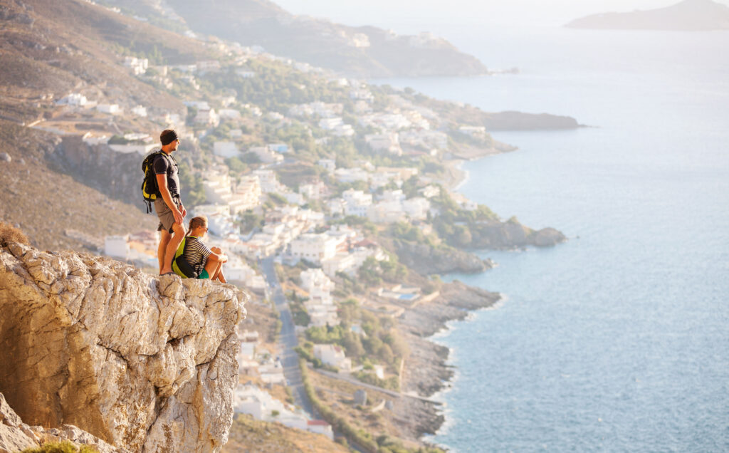 Couple on rock high above village in Kalymnos, Dodecanese, Greece