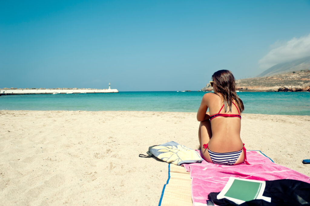 Young woman on a sandy beach in Kasos island, Dodecanese Greece