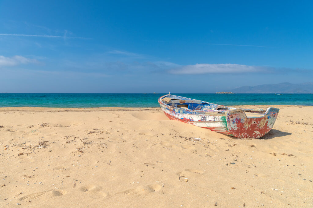 Abandoned fishing boat on one of the most beautiful beaches in the world in Naxos island, Cyclades, Greece