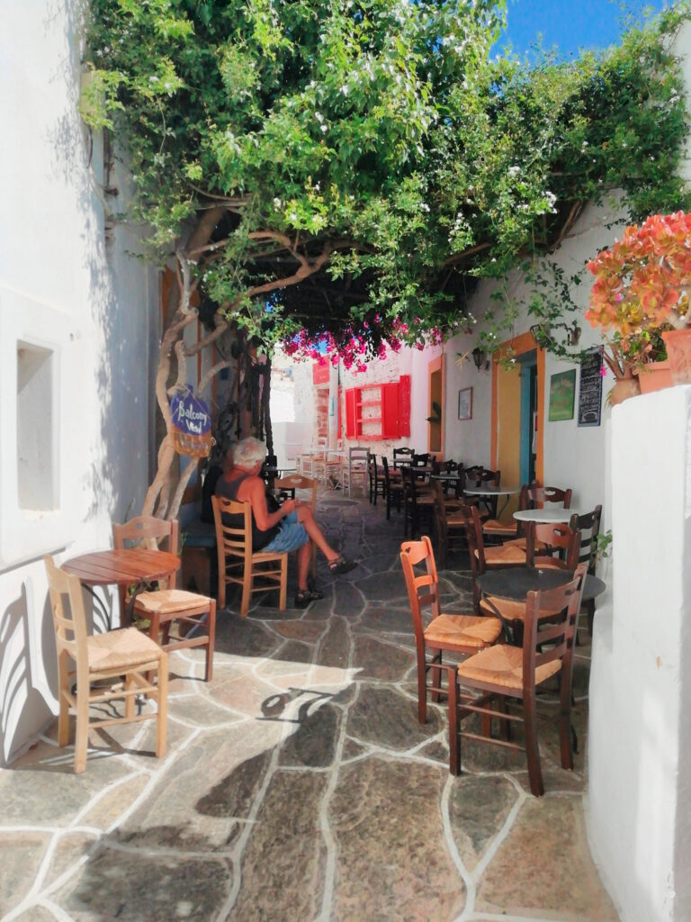 A narrow alley with a cozy cafe in the old historic Chora (village), the island of Sikinos, Greece