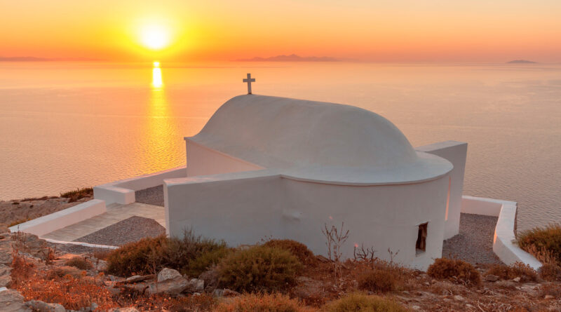 Sunset above small white church in Sikinos island, Greece