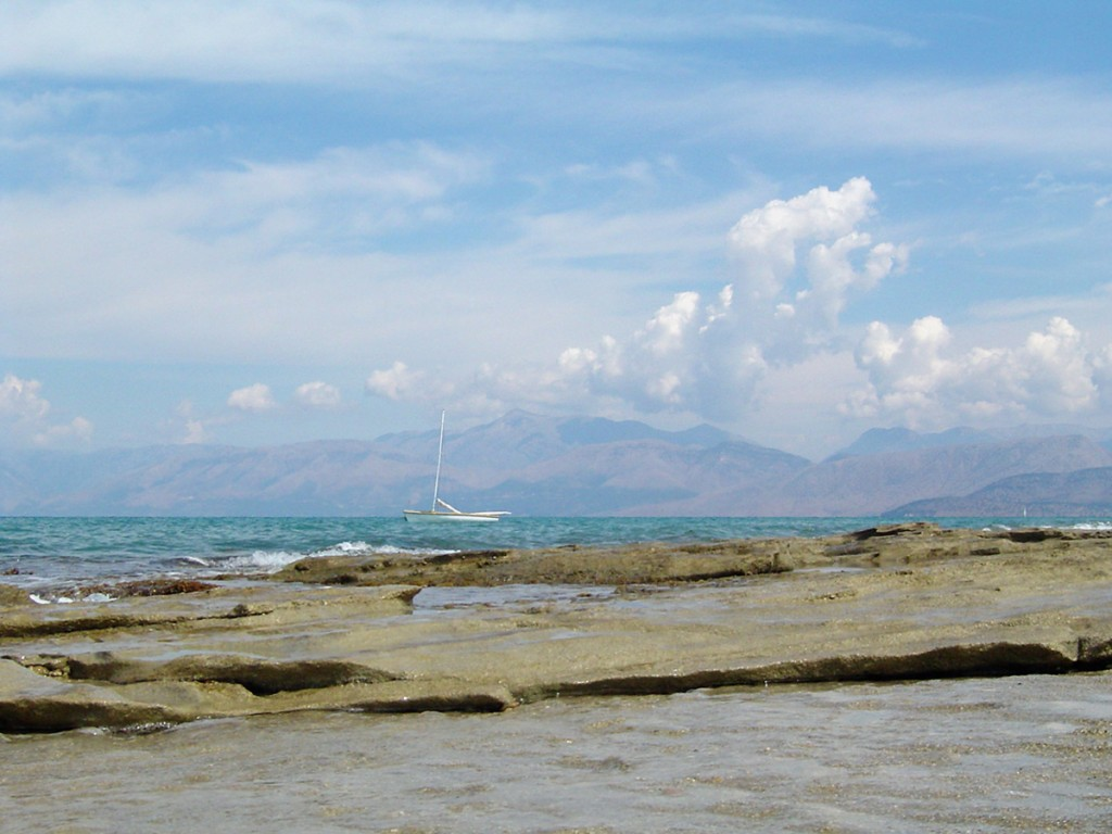 Beach of stone slabs and a boat under a blue sky, Albanian mountains to be seen in a distance