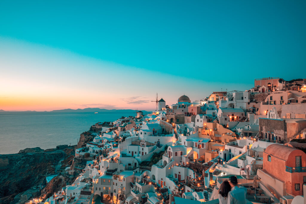 Fantastic sunset landscape of famous travel and vacation destination. Luxury summer adventure concept. Wonderful view of Oia village, Santorini, Greece. Hotels with pools and amazing architecture