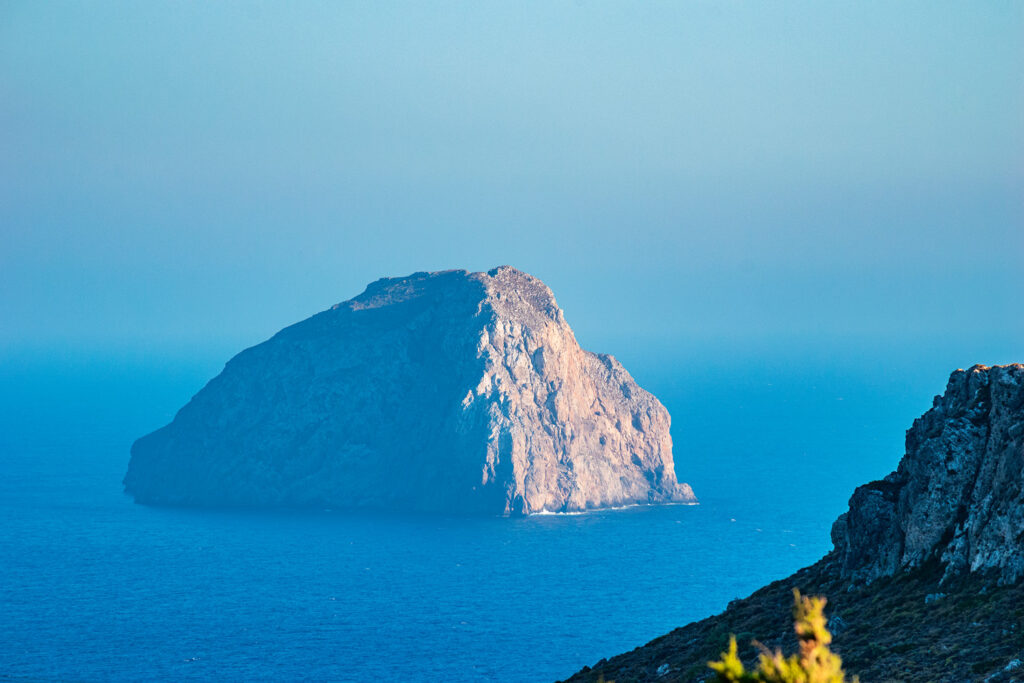 "Islet of Hytra (or Avgo meaning ""egg"" close to Kapsali in Kythira island Greece, The steep and rocky islet is decorated by the yellowish semprevivum, and nesting falcons"