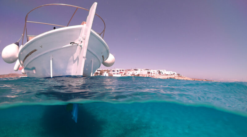 Above and below underwater photo of traditional fishing boat docked in turquoise clear sea in port of Koufonisi island, Small Cyclades, Greece