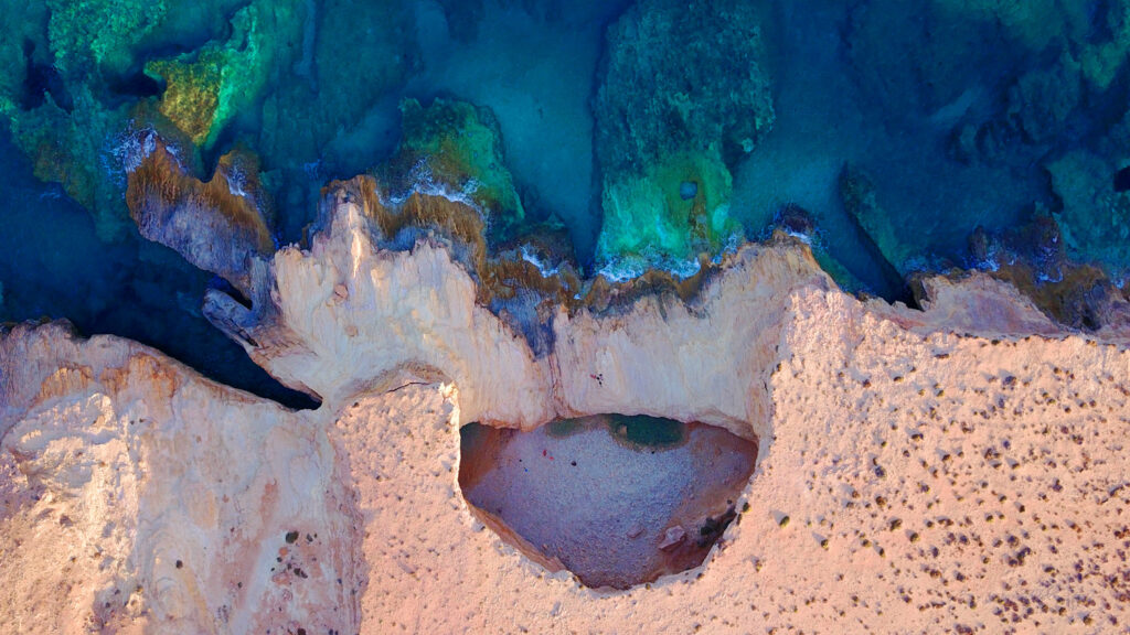 Aerial view of beautiful volcanic cave of Gala with deep blue - turquoise clear sea, Koufonissi island, small Cyclades, Greece