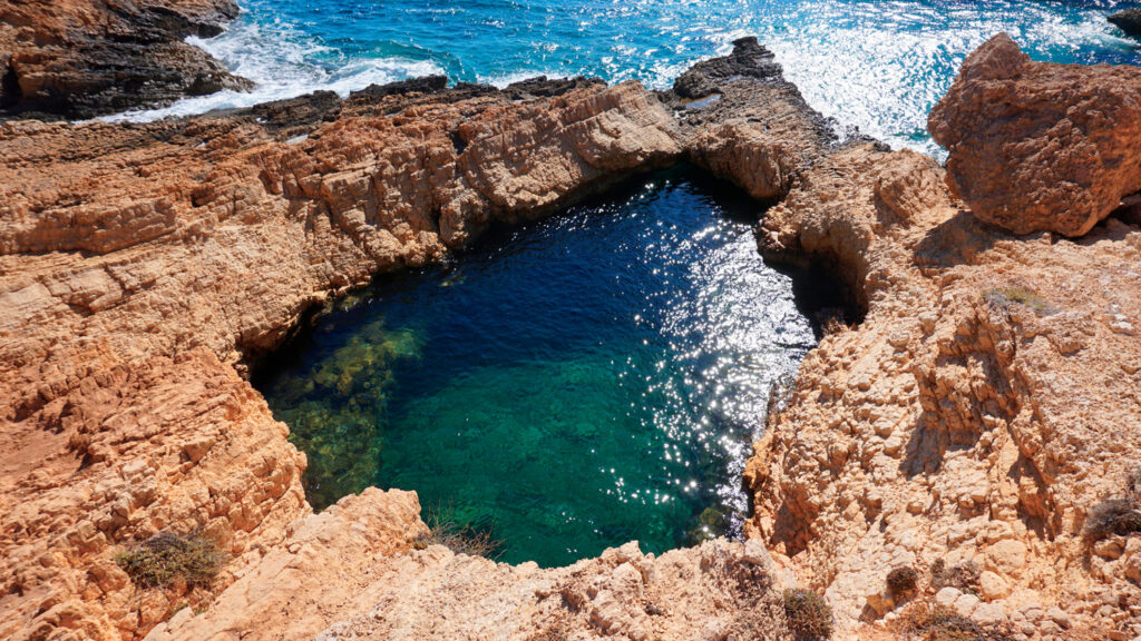 Devil's Eye, a rocky volcanic round lagoon formation in Koufonissi island with sapphire clear waters, Cyclades, Greece