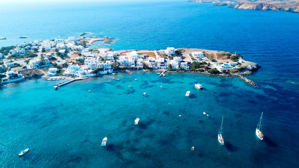 Aerial view of the fishing village of Polonia with traditional fishing boats docked in Milos next to the island of Kimolos, Cyclades Greece