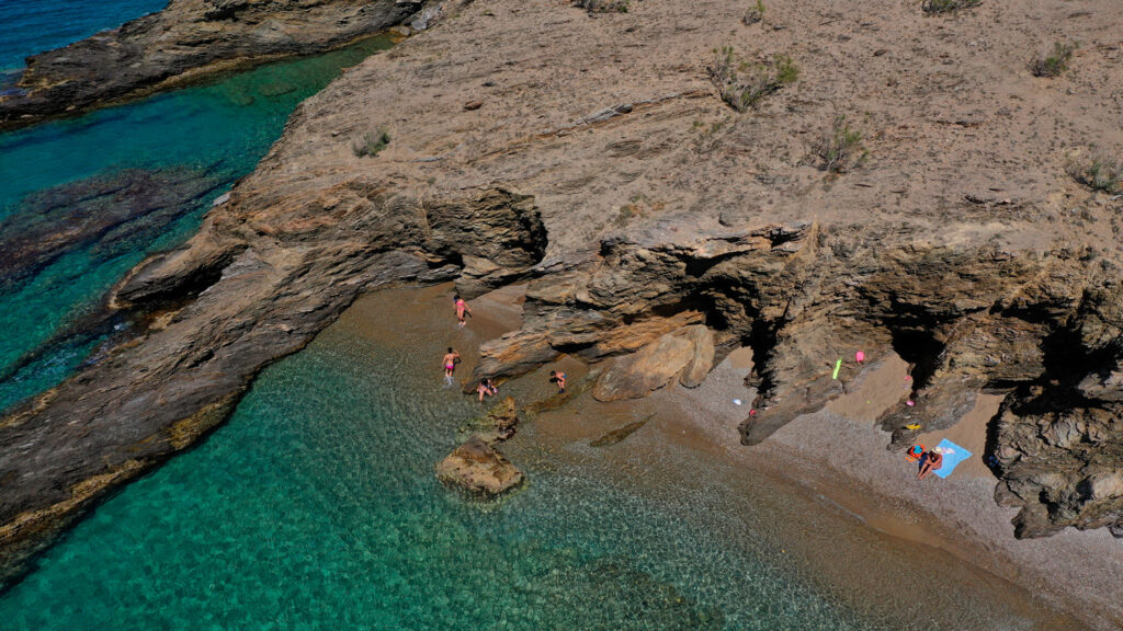 Latinaki beach with crystal clear sea and rocky shore forming small caves, Folegandros island, Cyclades Greece