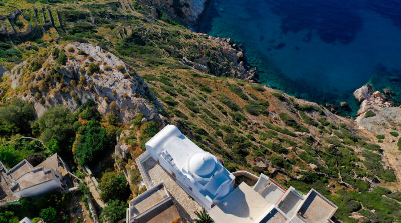 Whitewashed steep cliff church of Panagia Pantanassa in main village of Folegandros island with stunning views to Aegean Sea, Cyclades, Greece