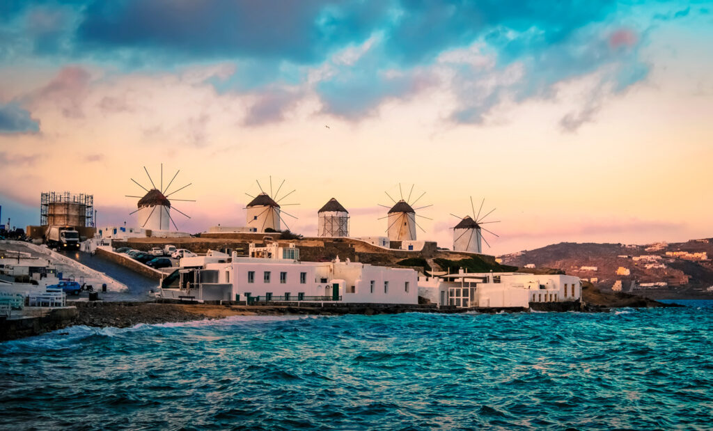 Sunset view of Mykonos seafront with windmills, Cyclades Greece