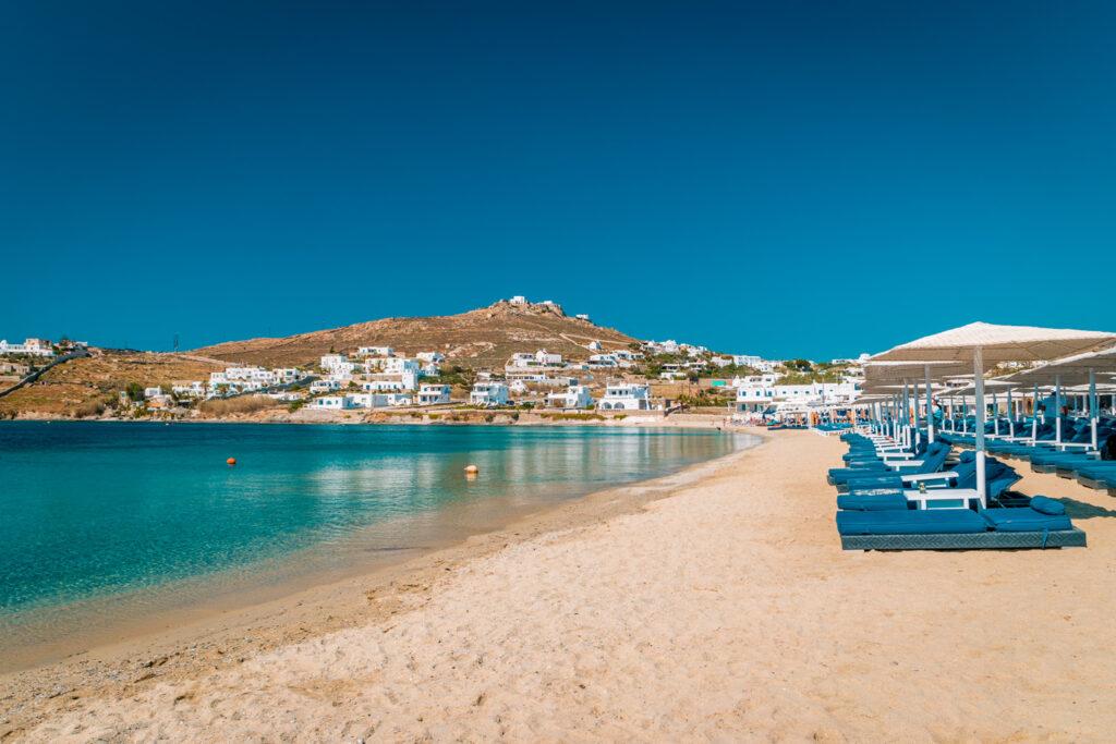 Mykonos island, famous Ornos beach organized with sun beds emerald clear water beach of Ornos in island of Mykonos, Cyclades, Greece