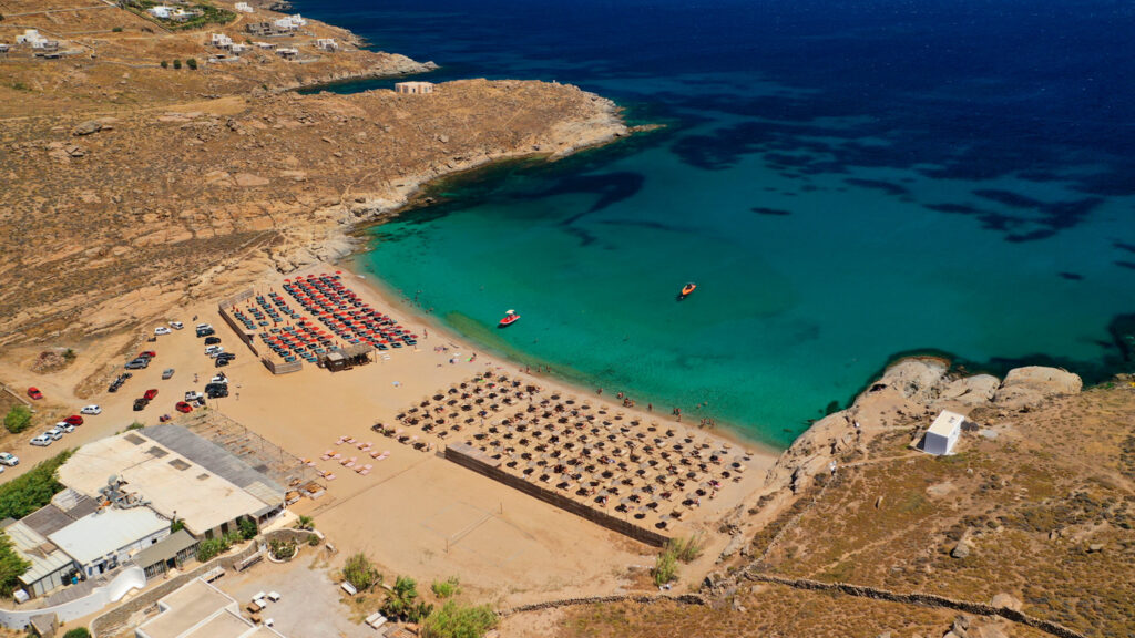 Drone photo of famous organized with sun beds and umbrellas beach of Lia with emerald clear sandy sea shore, Mykonos island, Cyclades, Greece