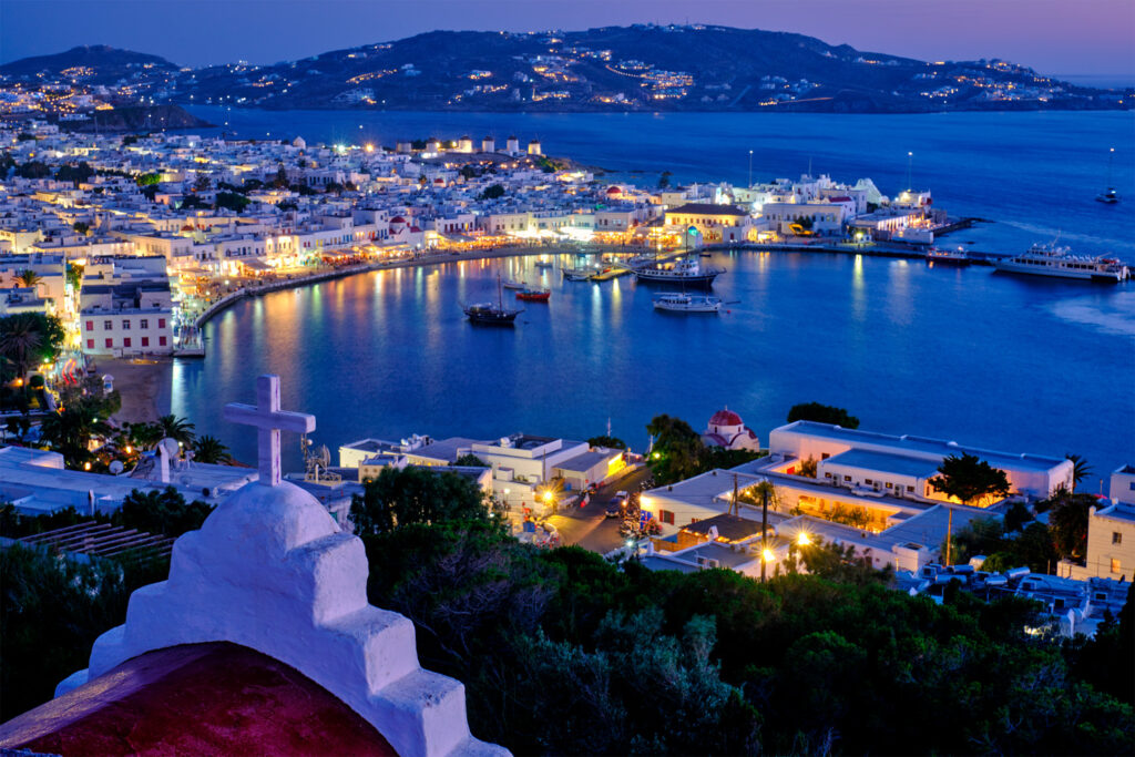 Mykonos port with the famous windmills and small boats at night, Mykonos, Cyclades Greece