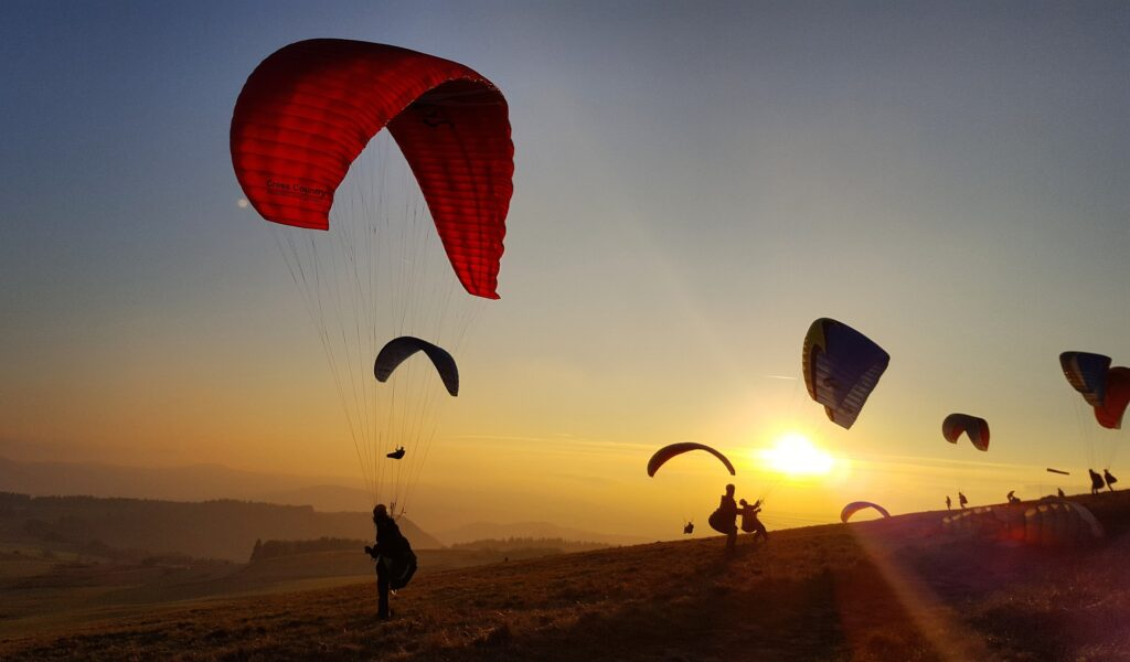 travel to greece - parachute jumpers and skydivers at sunset