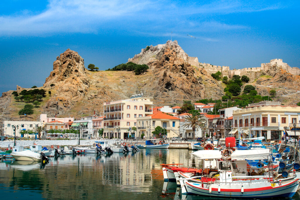 Idyllic port with fishing boats and the old castle on the hill, Lemnos, North Aegean island Greece