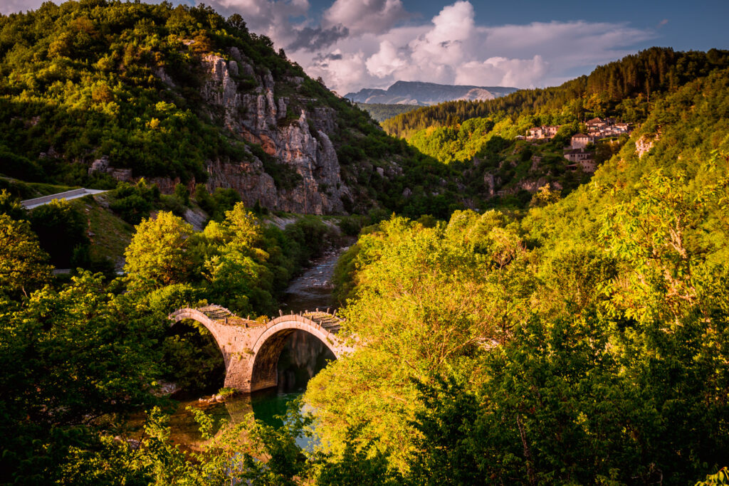 Plakidas Bridge with Kipi village in background - Arches stone bridge of Kalogeriko on river Voidomatis Central Zagoria Epirus Greece