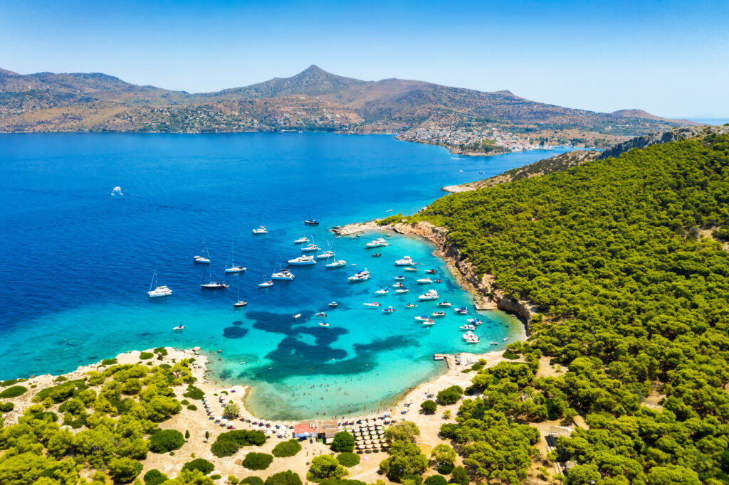 Aerial view of the beautiful beach of Moni island next to the village Perdika on Aegina island with turquoise sea in the Saronic Gulf, Greece