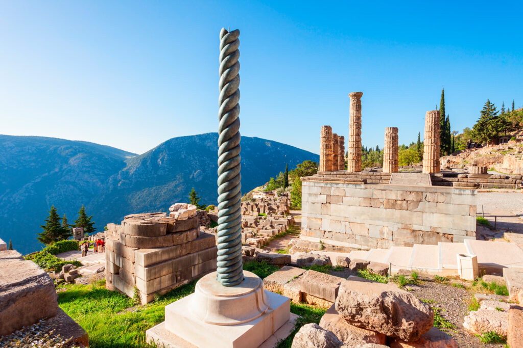 Serpent-Column-of-Plataea-and-Temple-of-Apollo-in-Delphi.-Delphi-was-an-important-ancient-Greek-religious-sanctuary-sacred-to-the-god-Apollo