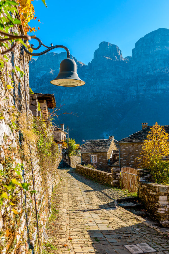 Traditional-architecture-with-narrow-stone-street-and-astraka-mountain-as-background-during-fall-season-in-the-village-Papigo-in-zagori-Greece