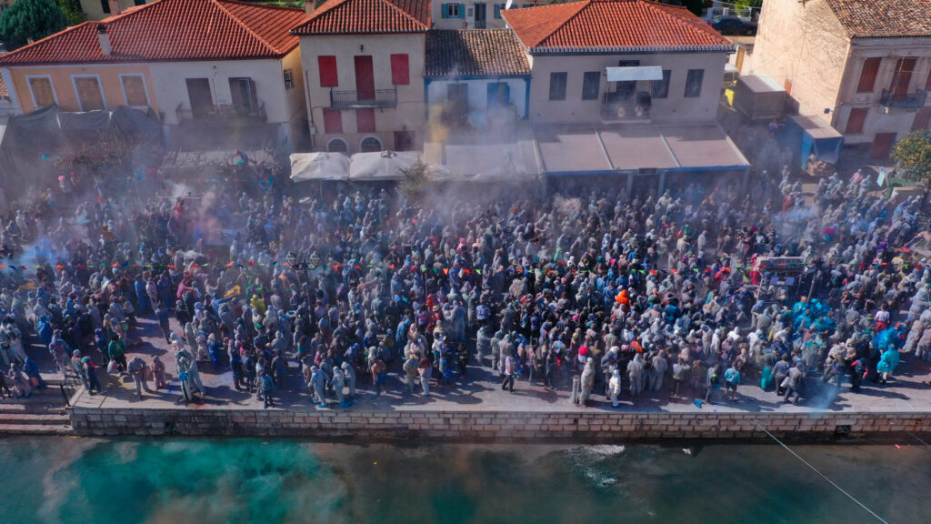 aerial-view-of-people-participating-in-traditional-colourful-flour-war-or-Alevromoutzouromata-part-of-Carnival-festivities-in-historic-port-of-Galaxidi-central-greece