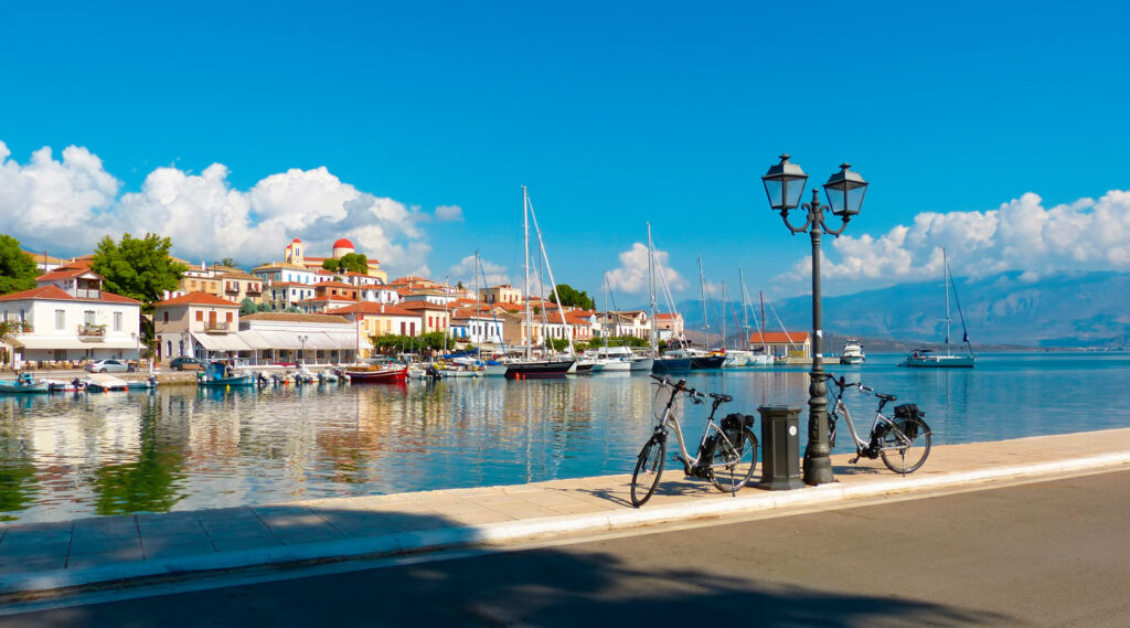 two-bicycles-boats-and-colorful-traditional-houses-at-the-seafront-of-galaxidi-fishermen-village-central-greece