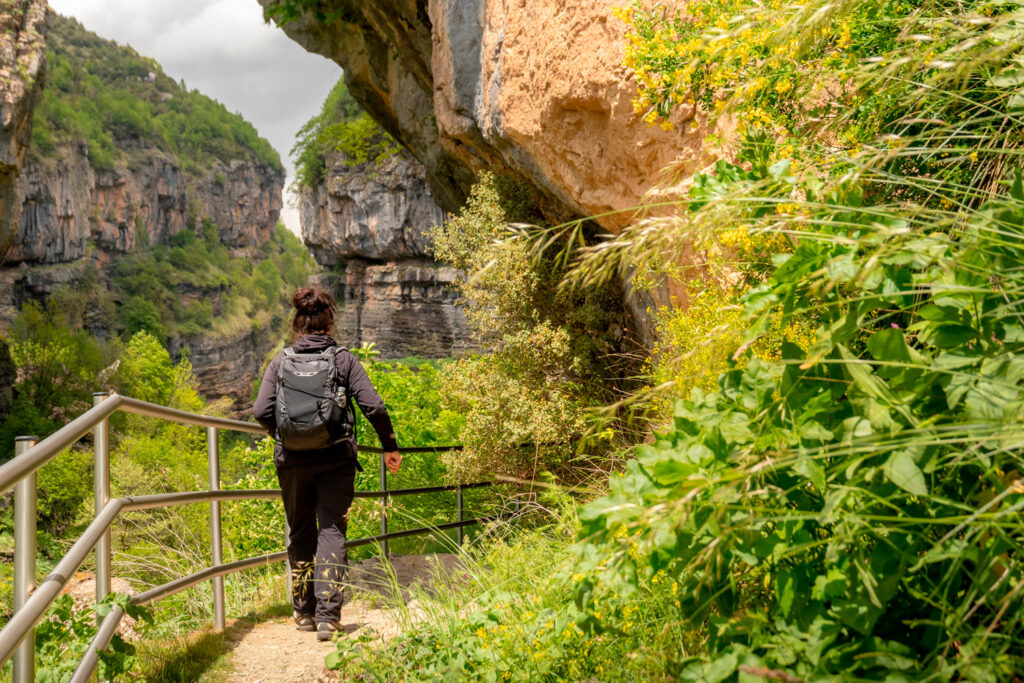 Woman with a backpack hiking in the mountains of the Tzoumerka nature reserve in Epirus, Greece