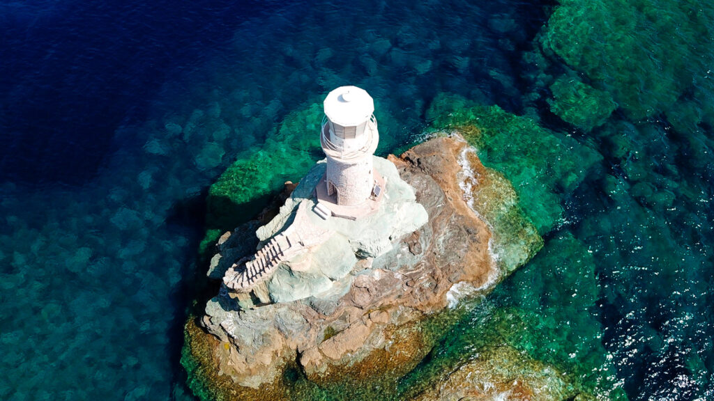 aerial-drone-bird-s-eye-view-of-iconic-lighthouse-of-tourlitis-in-port-of-andros-island-chora-Cyclades-Greece