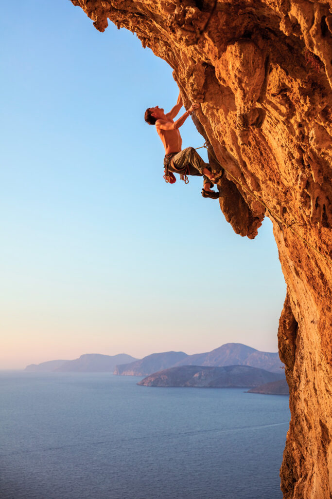 Rock climber on overhanging cliff in Kalymnos island, Dodecanese Greece