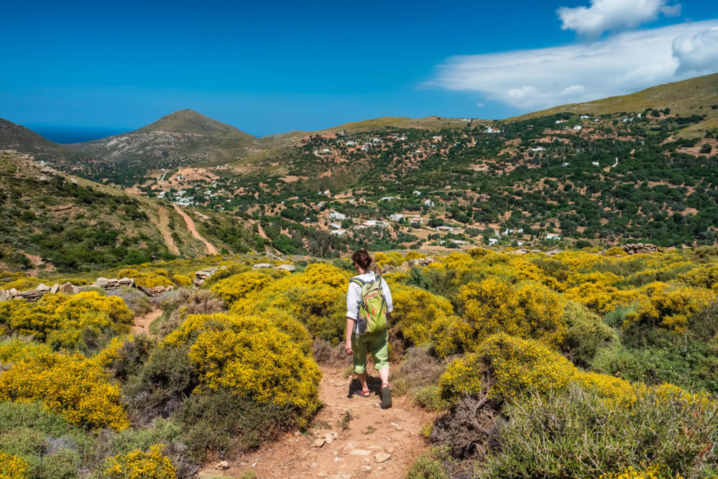 woman-with-a-backpack-hiking-on-a-hiking-trail-on-andros-island-cyclades-greece