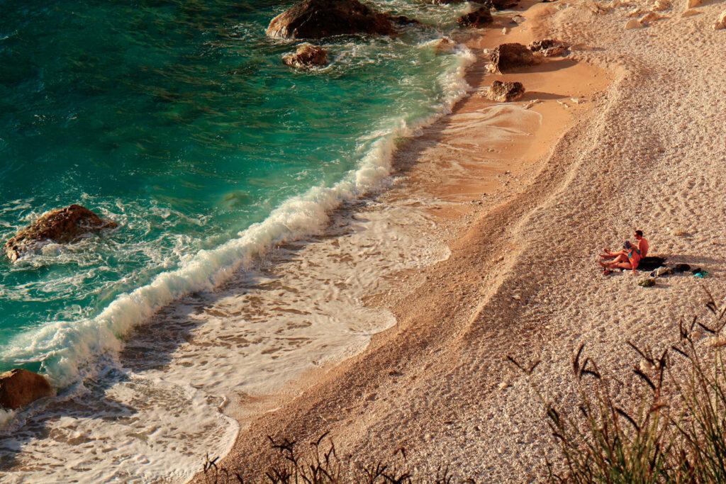 Erimitis beach in Paxos island, Ionian Sea Greece - Couple enjoying the sunset