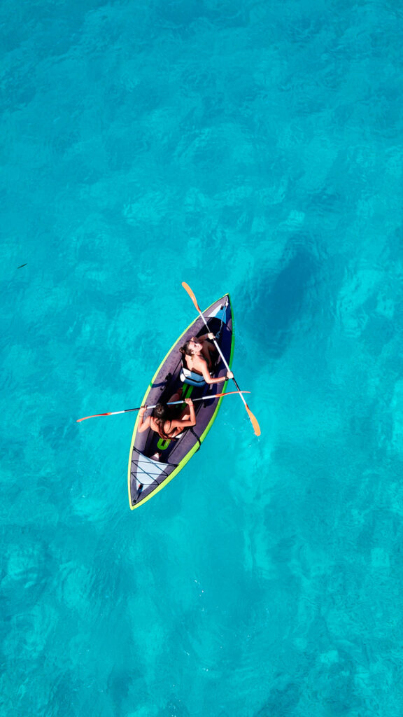 Two women canoeing from the beach of Voutoumi in Antipaxos island, Ionian Sea Greece