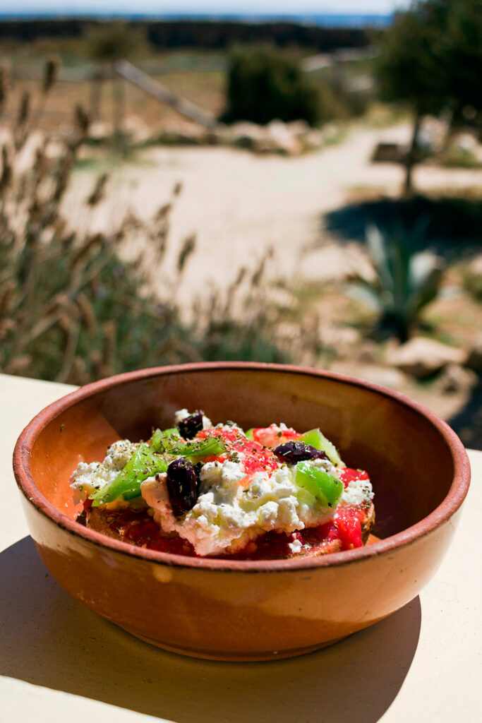 Dakos - a Greek appetizer with dried bread, tomatoes, feta or mizithra cheese with capers and oregano. Taken in Donoussa, Lesser Cyclades, Greece