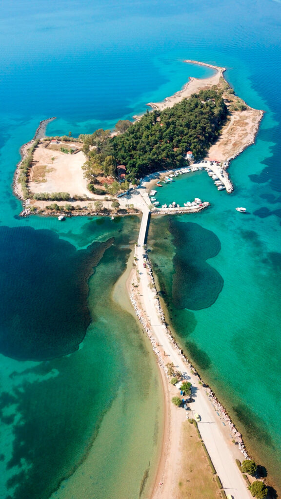 Aerial view of famous fishing village of Eretria with beautiful island of Dreams or Pezonisi connected by small piece of land, Central Evia, Greece