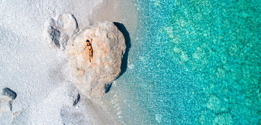 Aerial view of young woman sunbathing on a big rock in Skiathos, Sporades Greece