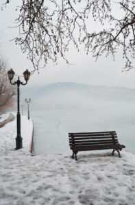 Bench on the banks of frozen lake Orestiada in Kastoria of Greece a overcast foggy day, West Macedonia Greece