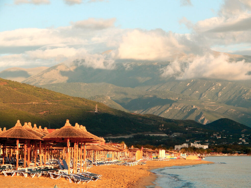 Deck chairs with umbrellas on the beach in Nei Pori and Mount Olympus partially covered with clouds in the morning, Greece