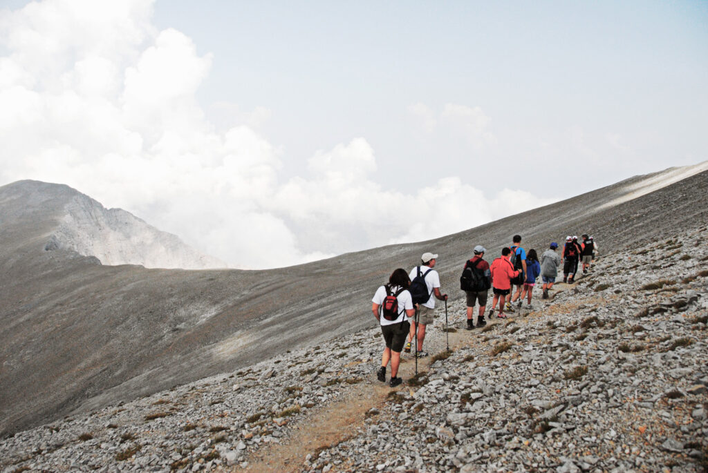 Mount Olympus, climbers walking under the Skolio summit (2.912 m.), the second highest peak of Olympus mt, going towards Christakis refuge, part of the way of the E4 European long distance path, Greece
