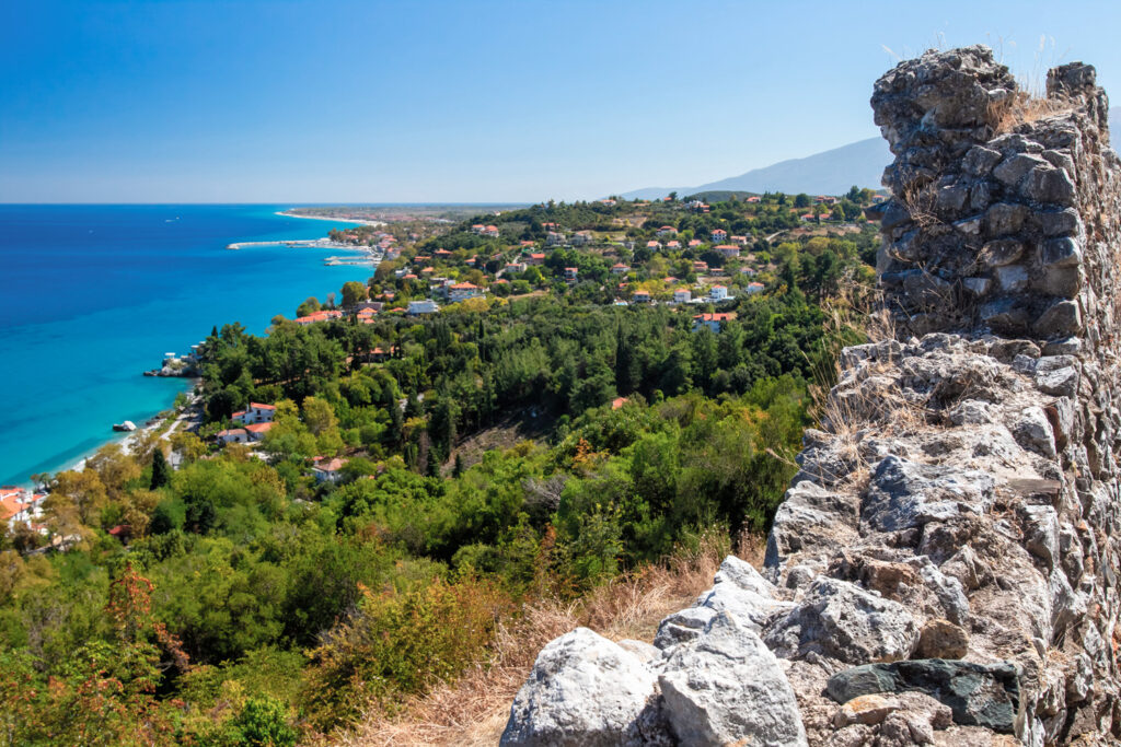 Greece.The Peninsula of Kassandra. Chalkidiki. Nea Phocea.The Village of St. Paul.View of houses on the coast in Greece. A fragment of an ancient wall, a village on the coast and the Mediterranean sea