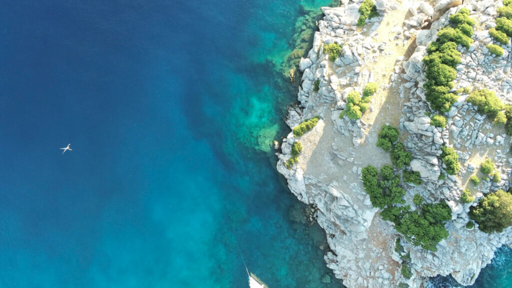 Aerial view of a lonely person swimming around Dokos Island in Greece.