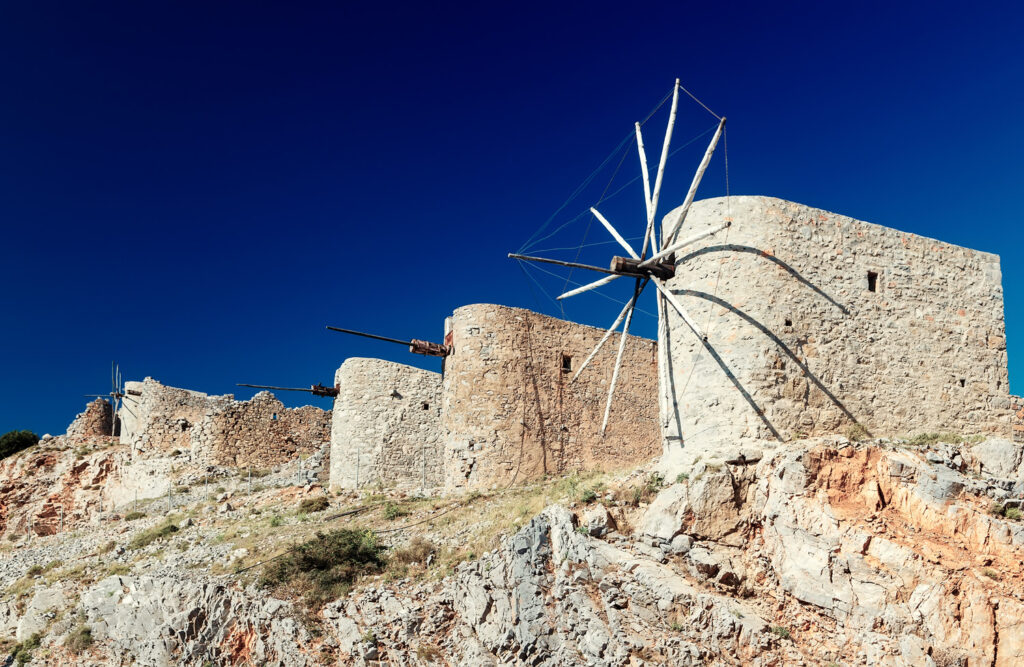 Ancient windmills against a bright blue sky of Lasithi Plateau in Crete, Greece